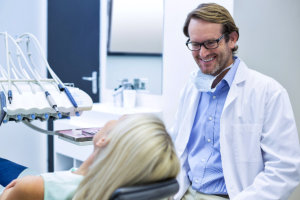 a male dentist smiling to a patient